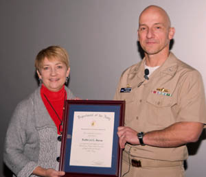 Capt. Brian Durant presents the Navy Meritorious Civilian Service Ward to Kathryn Burns