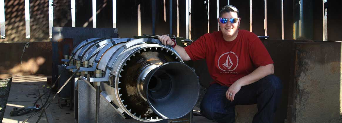 Naval Surface Warfare Center Dahlgren Division test engineer Lanie Pepitone poses with a Standard Missile rocket motor.