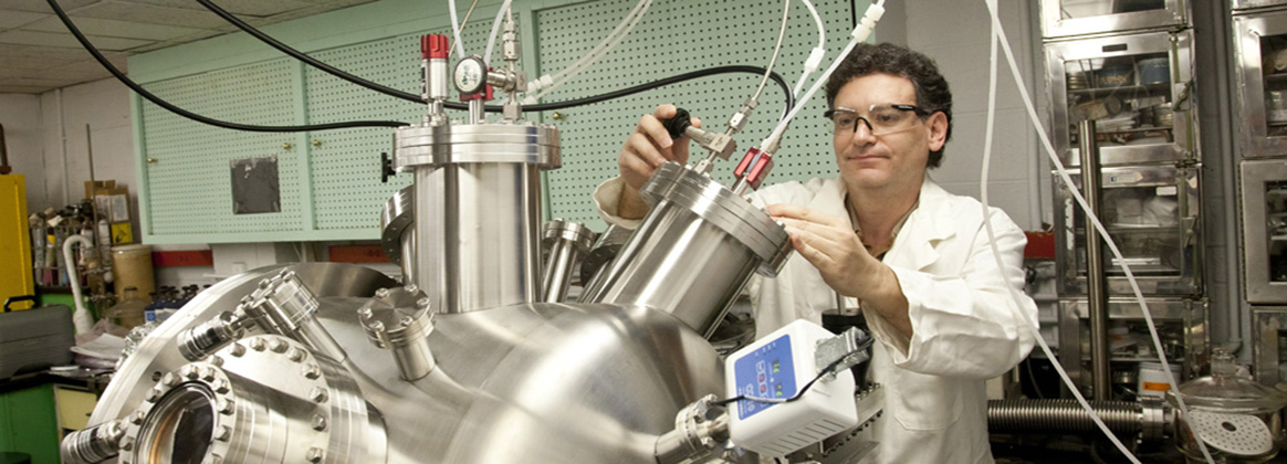 An NSWC IHEODTD Scientist adjusts the flow of argon gas into a custom designed vacuum deposition chamber used to make novel energetic materials.