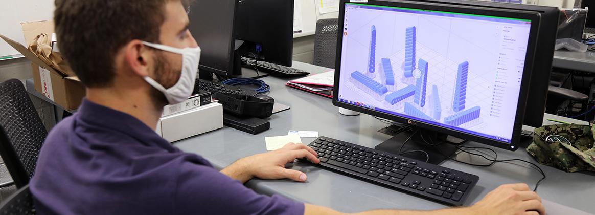Engineering Technician Adrian Wos reviews 3D models of potential Fiber Optic Sensing System (FOSS) housing units