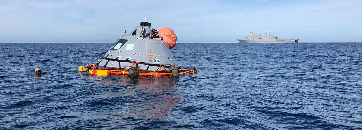 Sailors assigned to Explosive Ordnance Disposal Mobile Unit 11 and NASA personnel retrieve a boilerplate test article during an Underway Recovery Test (URT)