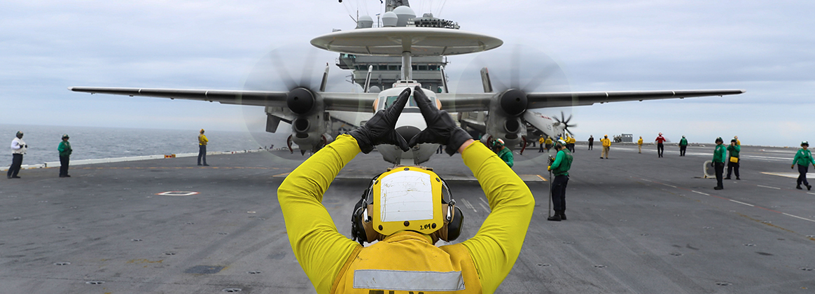 Aviation Boatswain's Mate (Handling) 3rd Class Trevor Prosser directs an E-2D Hawkeye
