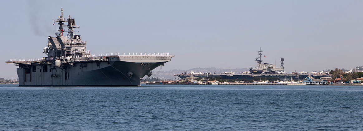 USS Tripoli (LHA 7) passes the USS Midway Museum as it arrives at its new homeport at Naval Base San Diego.