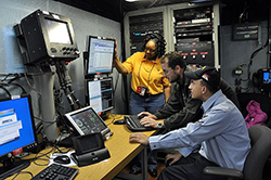Fran White, left, a civil service employee at Space and Naval Warfare Systems Command, Systems Center Atlantic, and Clayton Bush, a Tactical Networks (PMW-160) contractor, work with Information Systems Technician 2nd Class James Rago to troubleshoot the video teleconference system of a video information exchange system aboard the aircraft carrier USS Ronald Reagan (CVN 76). PMW-160 and SPAWAR provide the Navy with network fabric and services used by multiple shipboard tactical and business applications and systems and routinely install, maintain and train crewmembers in operational and maintenance procedures. (U.S. Navy photo by Rick Naystatt/Released)