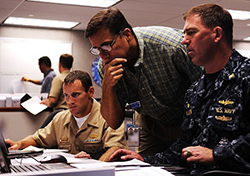 Lt. Cmdr. Gregg Bento, left, assigned to Commander, Navy Region Hawaii (CNRH), Shawn Morrissey, CNRH deputy of Operations, and Capt. John Polowczyk, commanding officer of Fleet and Industrial Supply Center Pearl Harbor, provide logistics support during the region operations center's Liberty Champion exercise. Liberty Champion is a simulated emergency management exercise that tests the Navy's rapid responses during crisis situations such as hurricane, earthquakes and oil spills. (U.S. Navy photo by Mass Communication Specialist 2nd Class Mark Logico/Released)