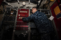 Electronics Technician 2nd Aryn Kriska, electronics material officer aboard the coastal patrol ship USS Squall (PC 7), tests equipment in the radio room before being heavy lifted to to the U.S. 5th Fleet operations area. Navy Cyber Forces performed an equipment upgrade and alteration on Squalls' communications systems during her availability in March and April 2013 in preparation for deployment. (U.S. Navy photo by Robin Hicks/Released)