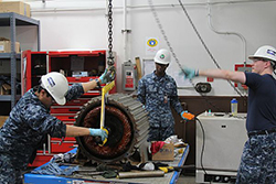 Sailors assigned to the Southeast Regional Maintenance Center (SERMC) remove the rotor from the inside of a fire pump motor taken from the guided-missile cruiser USS Philippine Sea (CG 58) in preparation for its complete overhaul. SERMC technicians perform these and many other maintenancGS10F164BAe actions routinely in supporting the Mayport fleet while earning a Navy Enlisted Classification. (U.S. Navy photo by Damage Controlman 3rd Class Mike Olsen/Released)