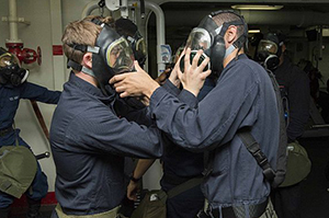 Sailors practice installing each other's C-2 canister filters on the MCU-2P gas mask during a chemical, biological and radiological (CBR) drill in the gym aboard the Wasp-class amphibious assault ship USS Essex (LHD 2). The Essex Amphibious Ready Group is operating in the U.S. 7th Fleet area of responsibility. (U.S. Navy photo by Mass Communication Specialist 2nd Class Christopher B. Janik/Released)