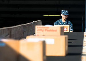 Logistics Specialist Seaman Miguel Torres, from San Diego, unloads cargo from a conveyor belt onto the enlisted quarterdeck of the aircraft carrier USS John C. Stennis (CVN 74). John C. Stennis is in port training for future deployments. (U.S. Navy photo by Mass Communication Specialist 3rd Class Andre T. Richard/Released)